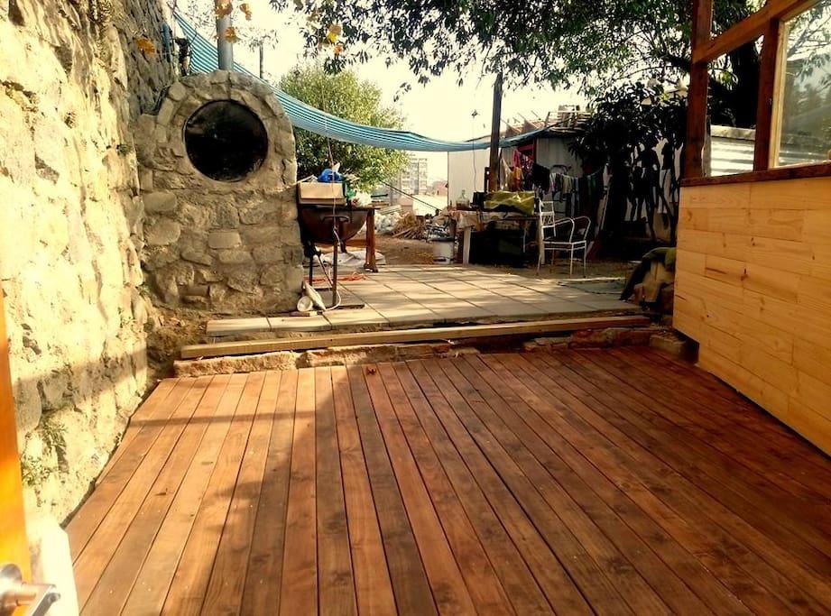 Terraza y patio con arbol, horno de barro y parilla.