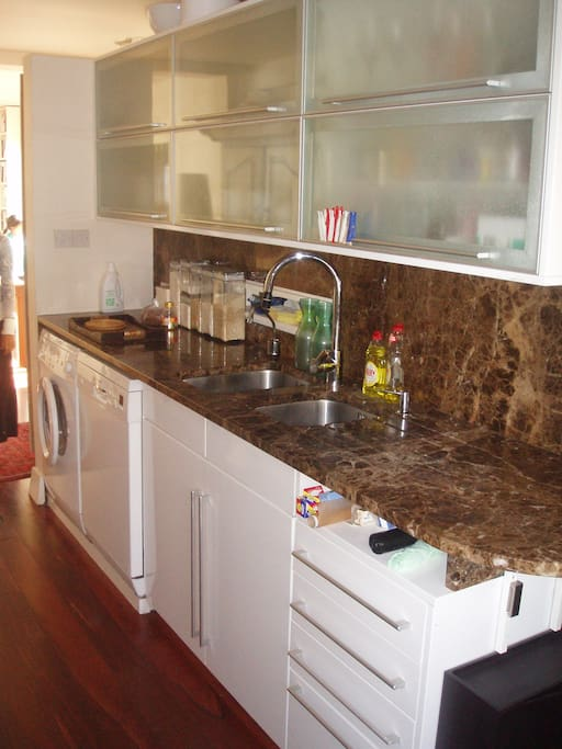 Kitchen with granite worktop and splashback, double sink and all basics foodstuffs - spices, dry herbs, cookbooks, etc
