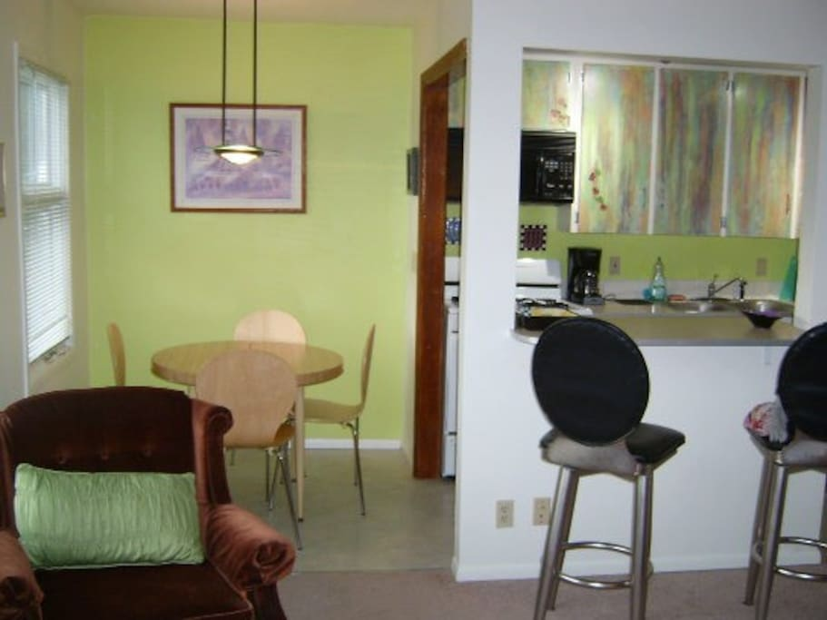 Full kitchen with breakfast bar and dinette set, bright and happy.