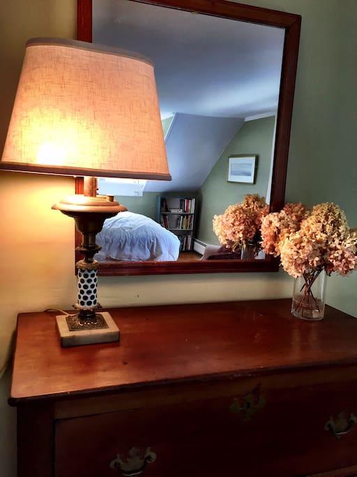 The Queen bedroom's antique lamp and bureau.