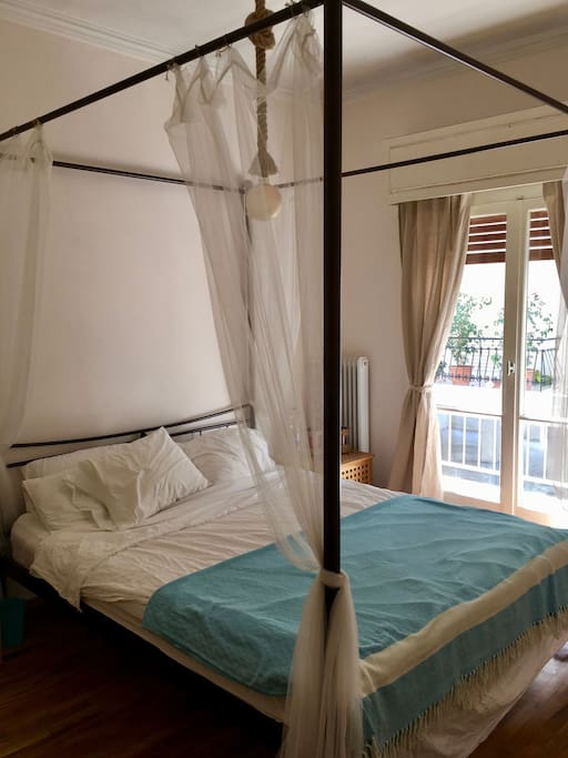 First bedroom with balcony and queen-size bed