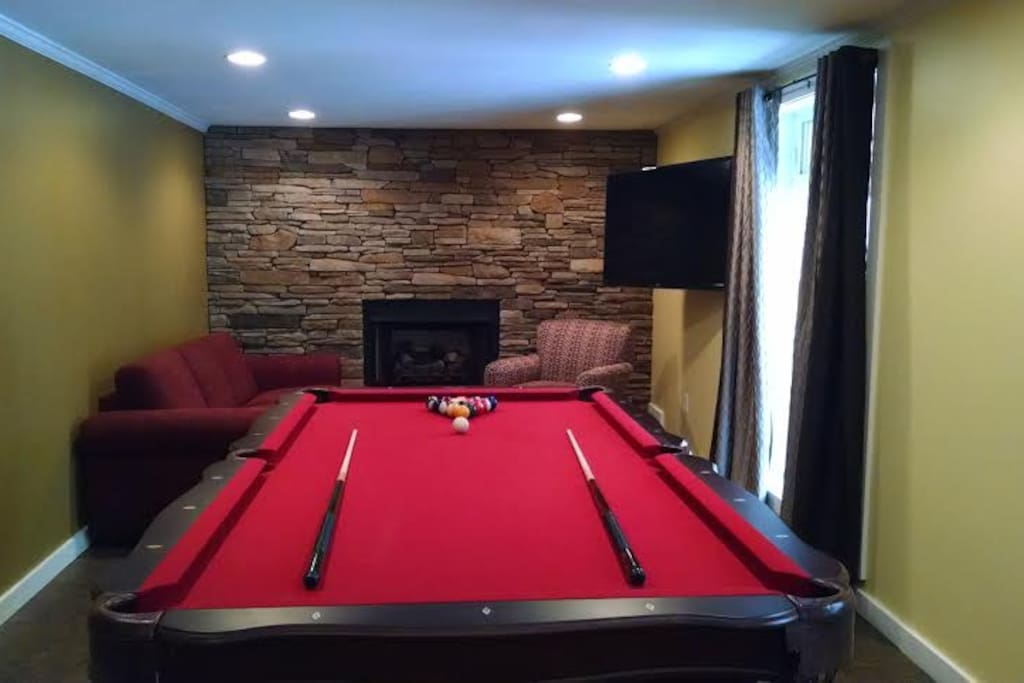 Downstairs game room complete with pool table and gas fireplace