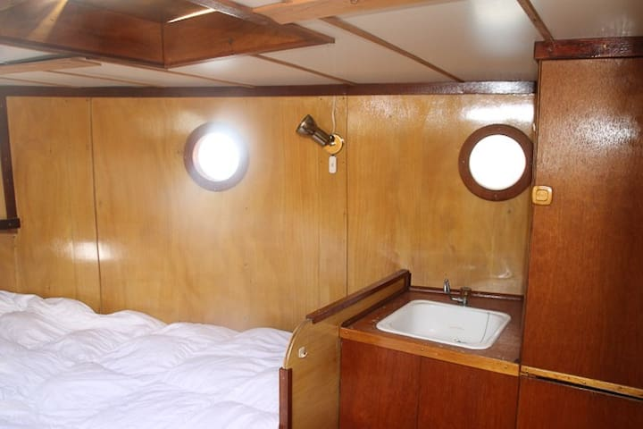 Bedroom in the front of the boat, with water, sink and closet.