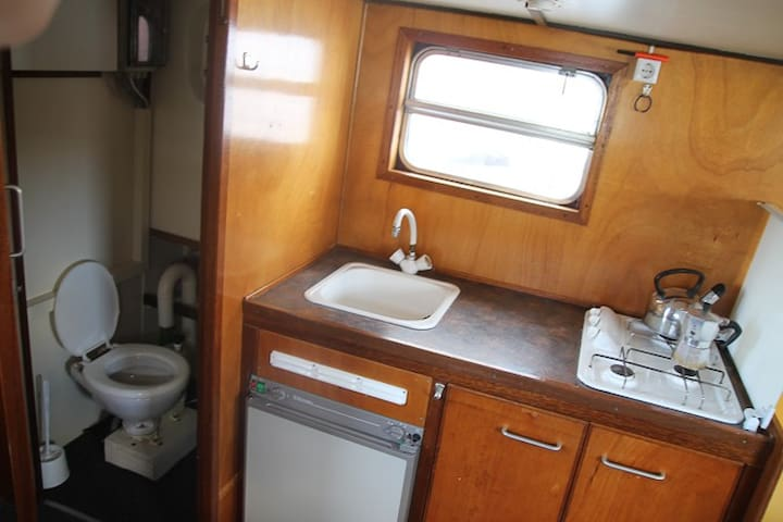 Kitchen with small fridge, stove, drinkable water, Nespresso machine. Toilet with handpump.