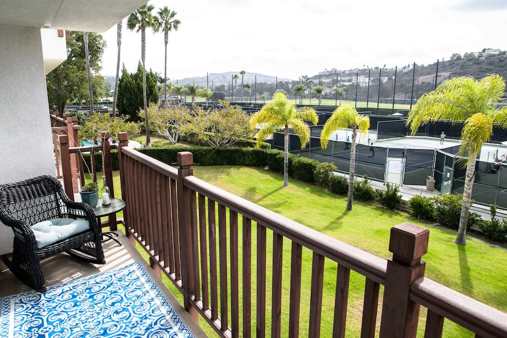 Balcony runs the length of condo with views of a resort's tennis courts