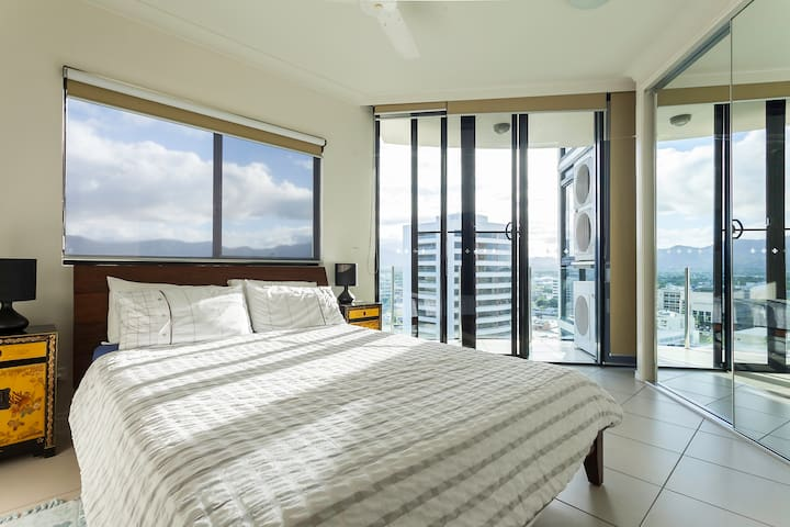 Very sunny and clean room with queen size bed and private balcony with outdoor chairs and table with city views.