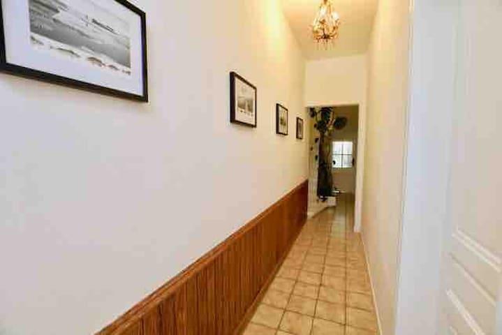 Entrée/couloir  Petit salon sur la droite  Cuisine au fond  Escalier accès premier étage