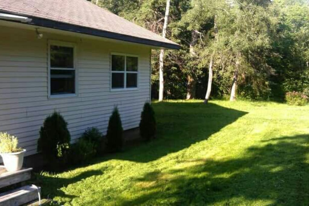 Large yard with picnic table and deck.
