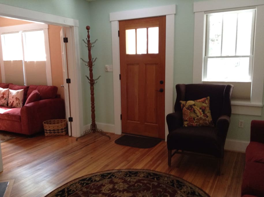 Entryway into home with sitting room on right and tv/movie room through french doors on left.