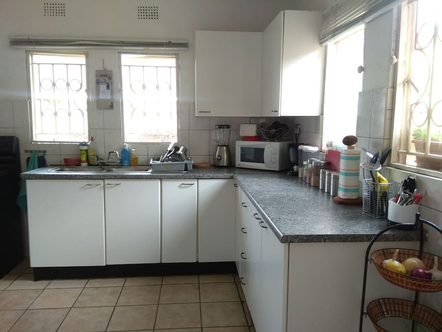Kitchen includes electric stove (with oven), fridge, microwave and coffee machine.