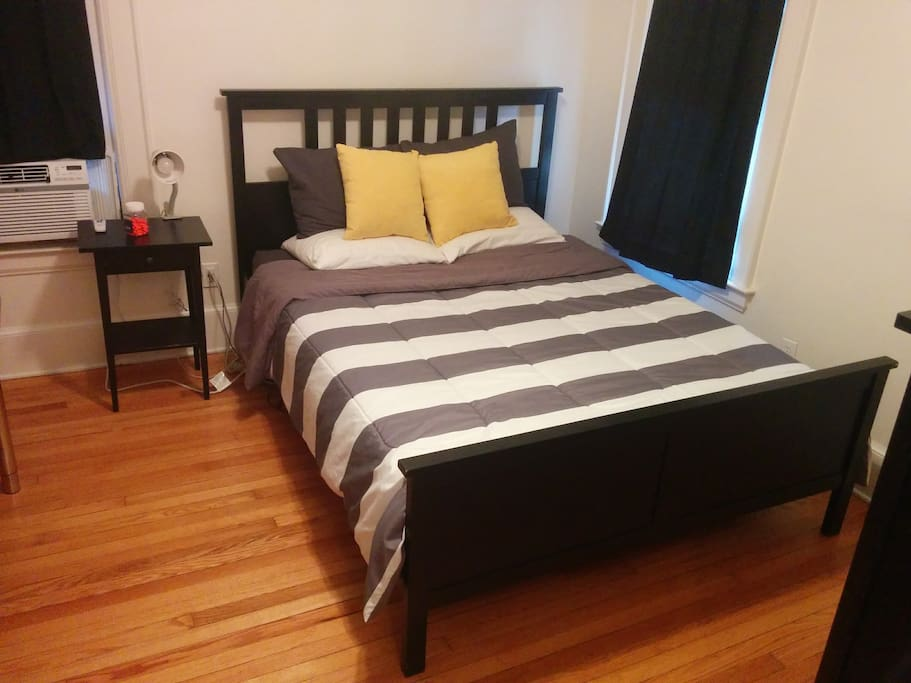 First guest bedroom - contains queen bed, dresser, desk, and night stand. Window A/C unit