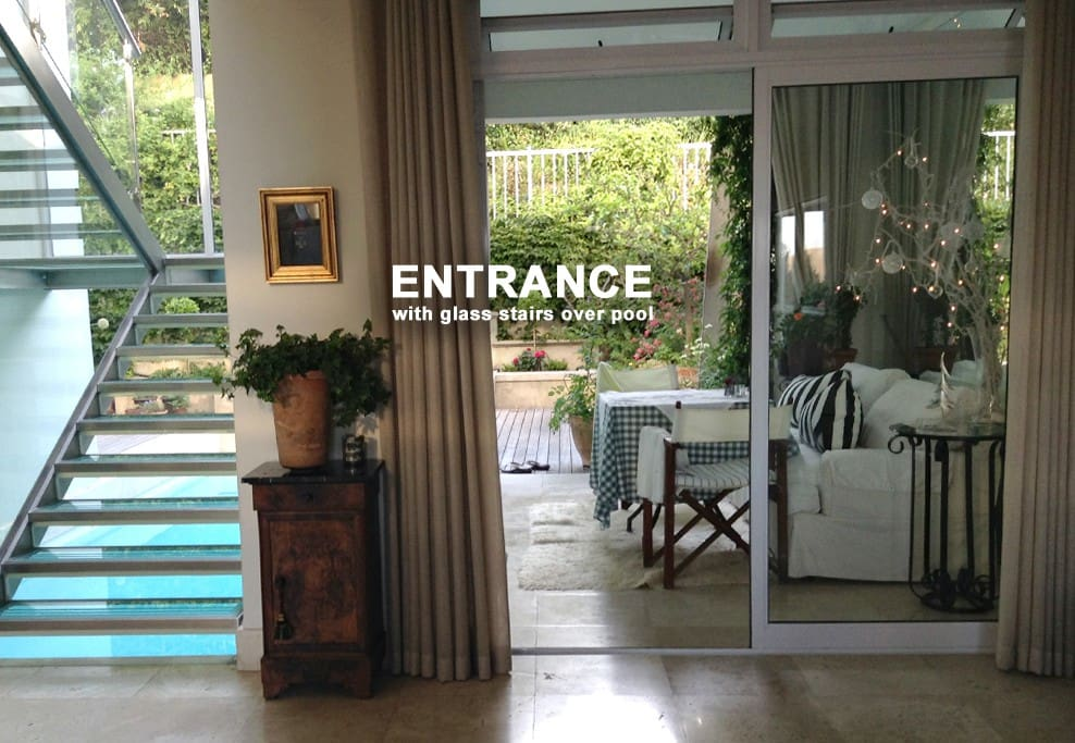 The entrance hall faces an unusual glass and steel staircase providing natural light throughout the central space overlooking the pool and the garden