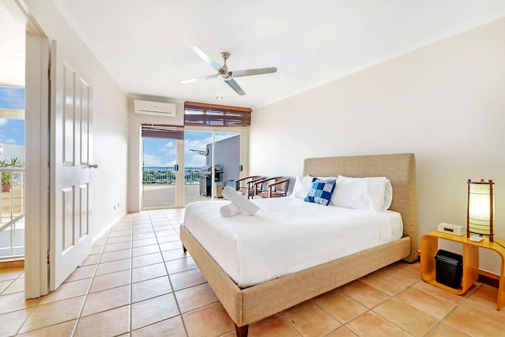 A huge, bright and breezy master bedroom has a queen bed, an en-suite bathroom and direct access to the beautiful rooftop deck.