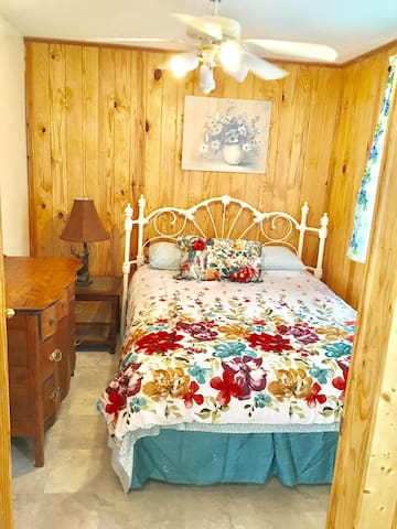 Master includes a quality, medium soft mattress, white iron queen bed, ceiling fan, separate AC/htr, knotty pine exterior walls, and door lock.    If you prefer quality log beds, instead of white iron, check out cabins #2, and 3 (or also 1 and 4 when they open soon)!