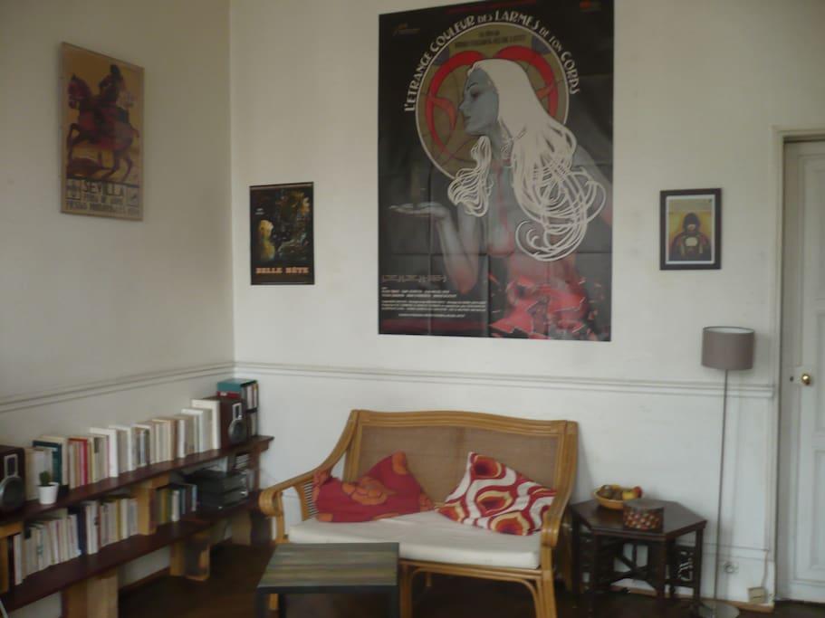 vaste salon, 1 banquette, nombreux livres (arts, littérature, sciences humaines), 2 grandes fenêtres ouvrant sur le balcon, chaîne hi-fi ...