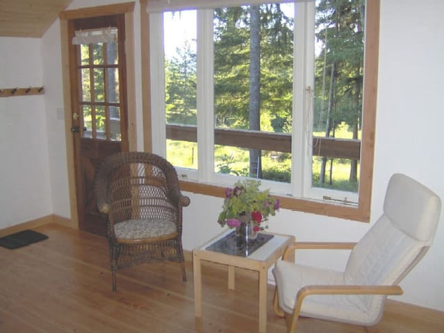 The sitting area also overlooks the acreage. Country wood plank floors are throughout the cottage.