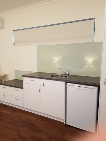 Kitchenette has a microwave, sink and small fridge