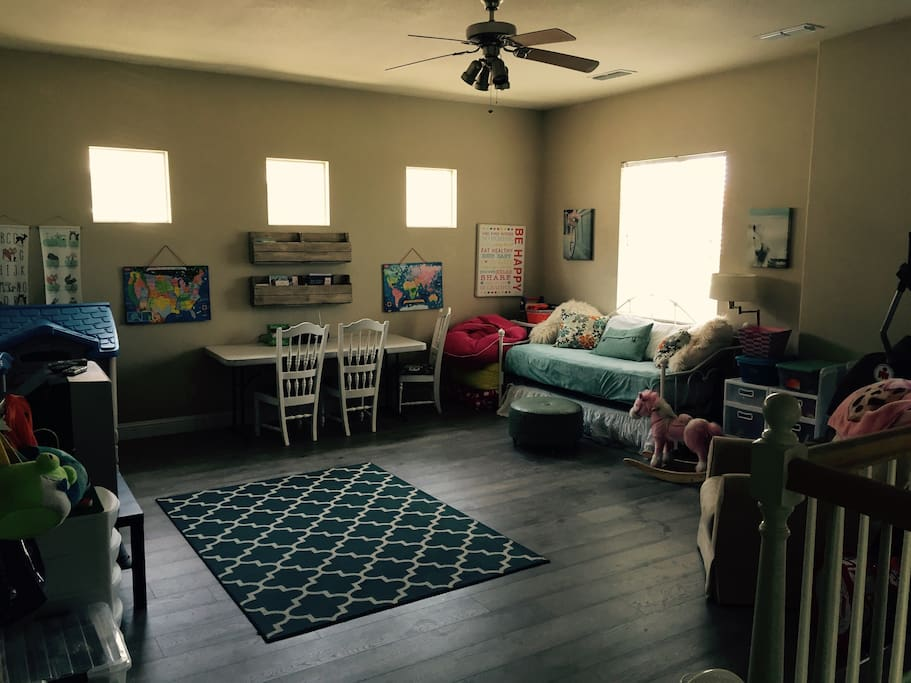 Spacious Loft playroom with TV, DVD player, trundle bed that sleeps two, and numerous toys.