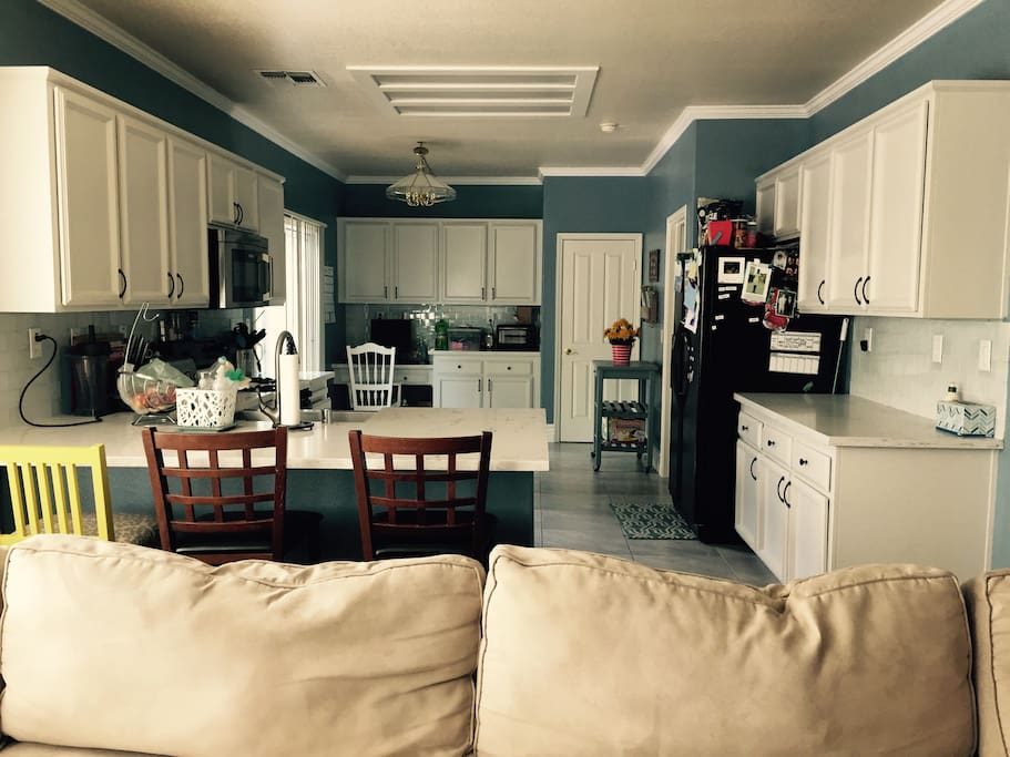Large kitchen with bar seating, microwave, stove/oven, dishwasher, and refrigerator.