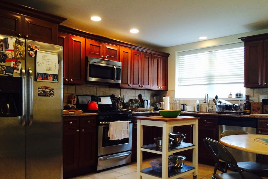 Full cook's kitchen with all amenities, including large stainless steel refrigerator, microwave, gas stove, and dishwasher