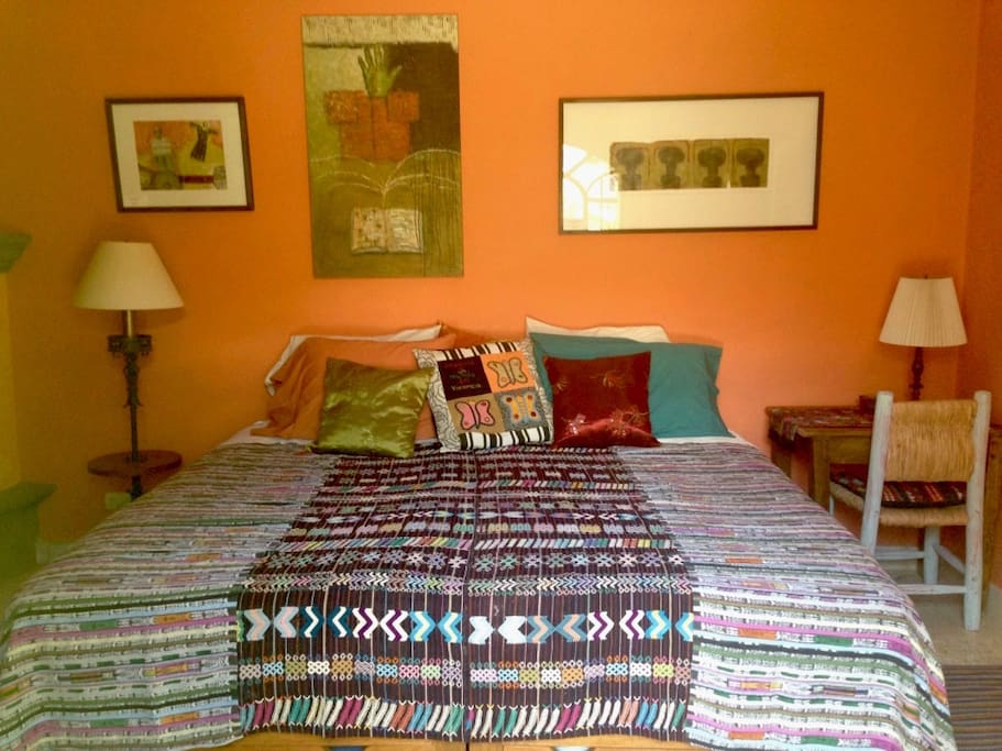 Comfortable bed, desk, reading lights, and the warm glow of papaya colored walls.