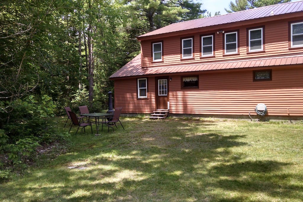 The back of the house with chiminea, picnic table, and lawn chairs.