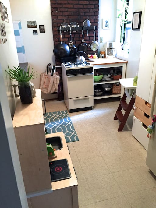 Fully stocked kitchen with exposed brick. A modern play kitchen for little cooks, too!