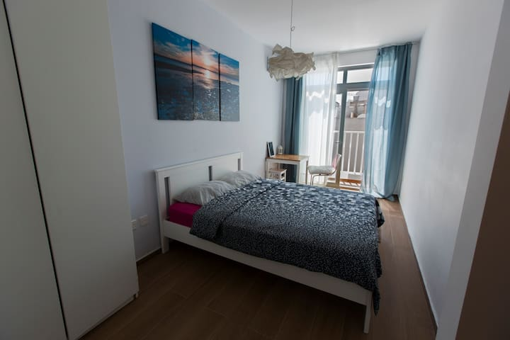 Spacious, silent and bright double bedroom with balcony, a wardrobe, fast WiFi, AC and a desk. The room comes with shared bathroom, a kitchen and a yoga-fitness room to workout. We offer 1 free yoga class.