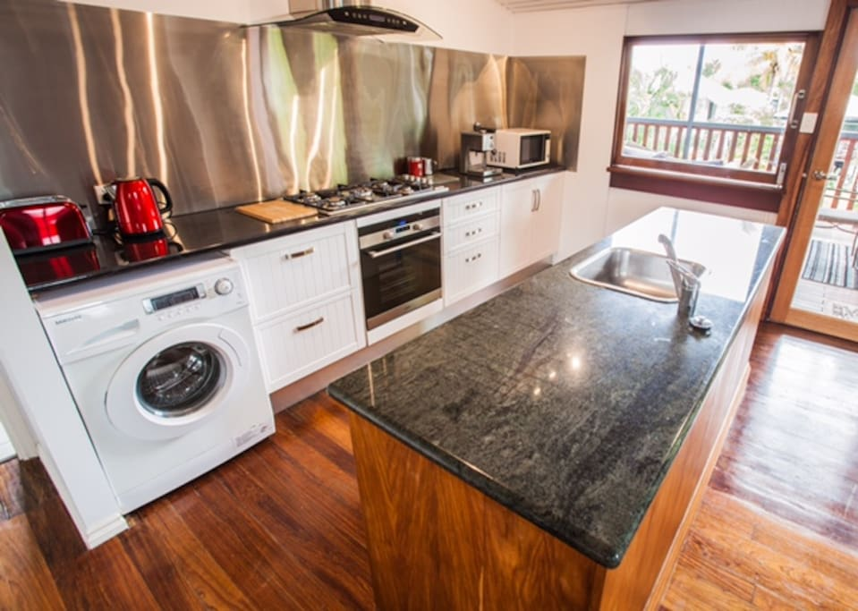 Galley kitchen features, gas cook top, oven, dish washer, island bar and sink, fridge/freezer and washing machine