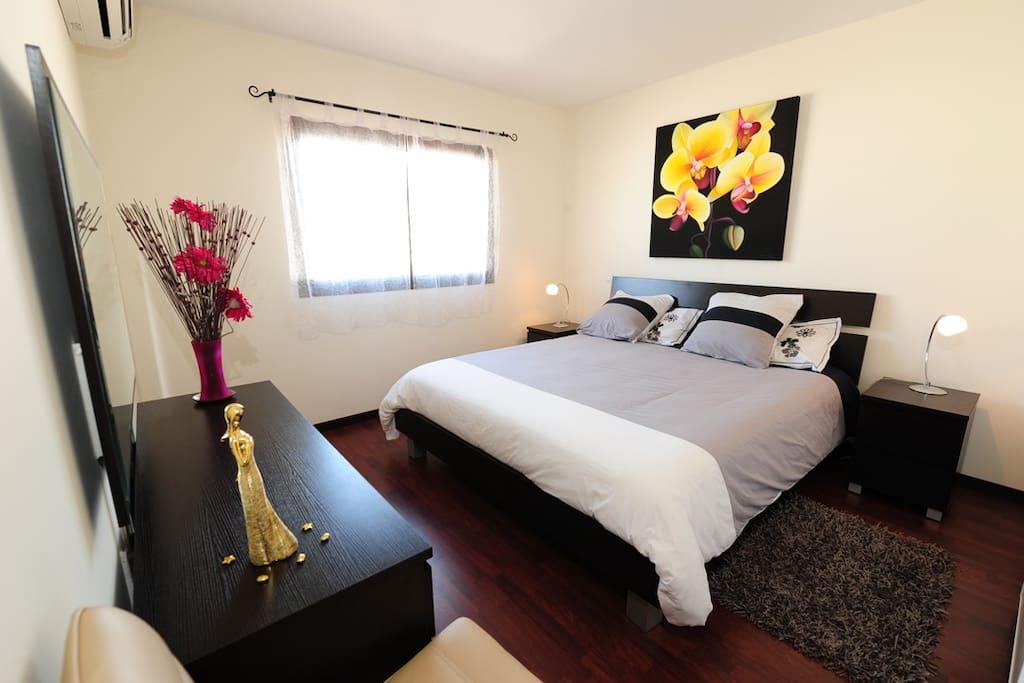 Chambre climatisée avec penderie et étagères, commode, miroir, fenêtre disposant d'un volet roulant automatisé.