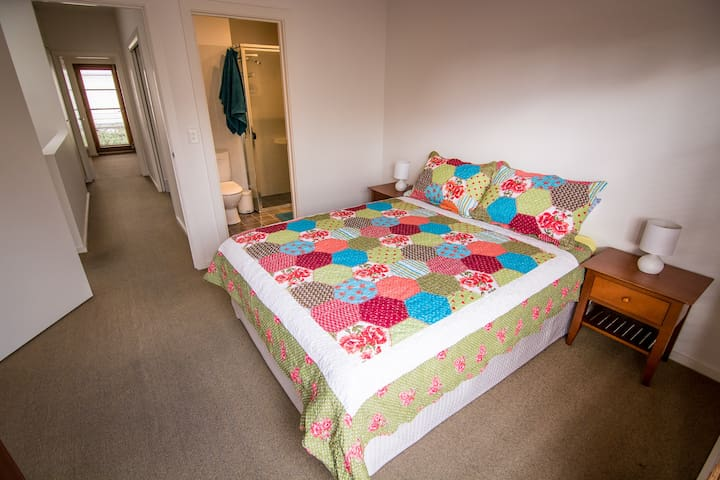 This bedroom has a queen bed, wall-to-wall wardrobe, a Juliette-balcony and ensuite bathroom.