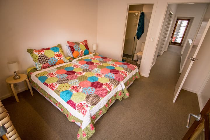 The second bedroom has two single beds, wall-to-wall wardrobe, a Juliette-balcony and ensuite bathroom.