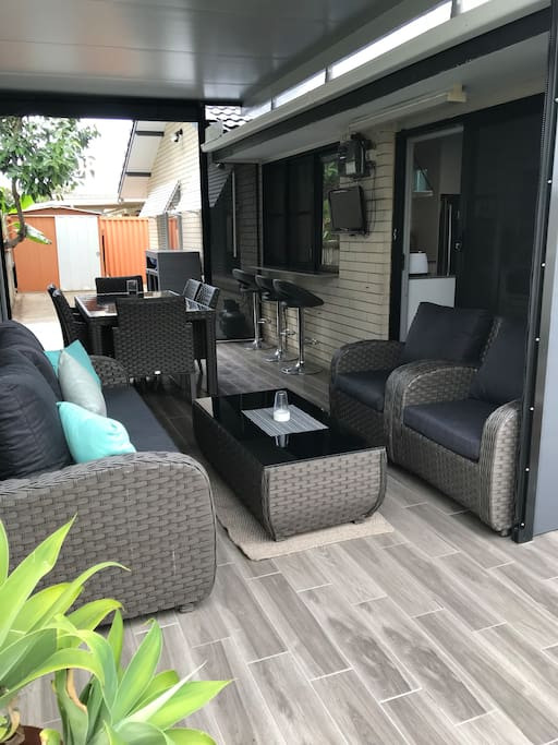 Undercover back entertaining area with dining table and relaxation area.