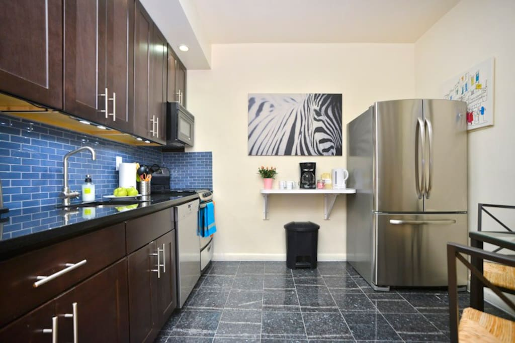 Elegant blue glass backsplash gives kitchen a vibrant feel