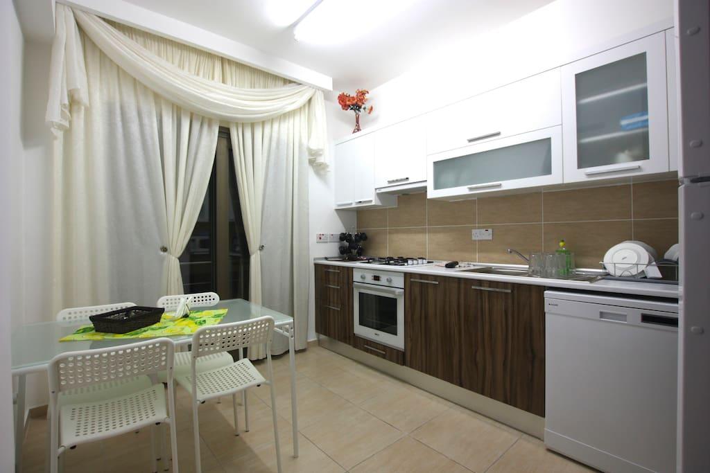 Кухня с посудомоечной машиной, микроволновкой и другой техникой