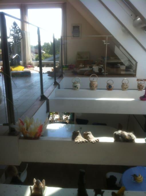 Åbent alrum mellem stue med udsigt til vandet og køkkenalrum.