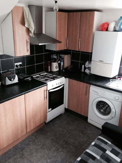 Kitchen, complete with big fridge, washing machine and gas oven.