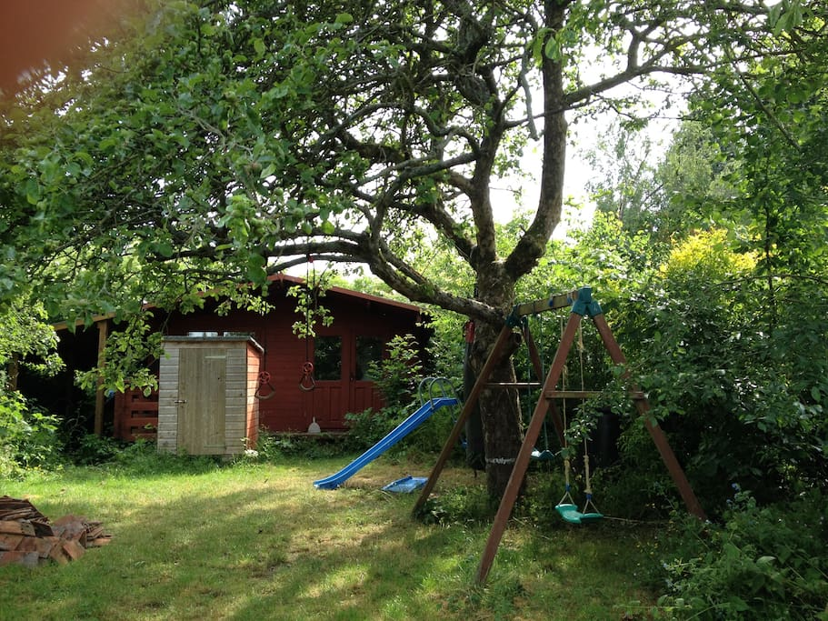 Fun back garden with trampolene, swing and slide for kids. BBQ and seating