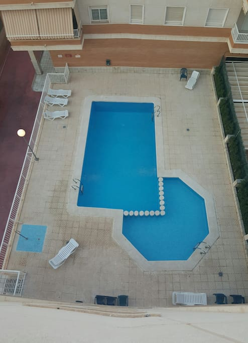 Community private Swimming pool with sunbeds and chairs