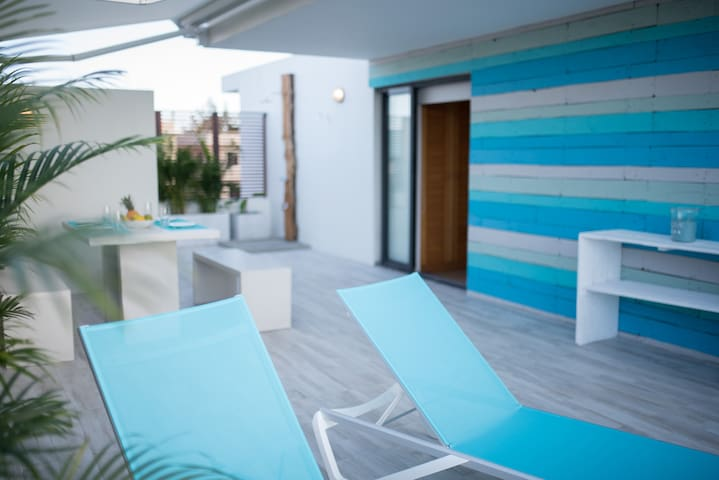 60m² Terrace with outdoor shower, table and sunbeds.