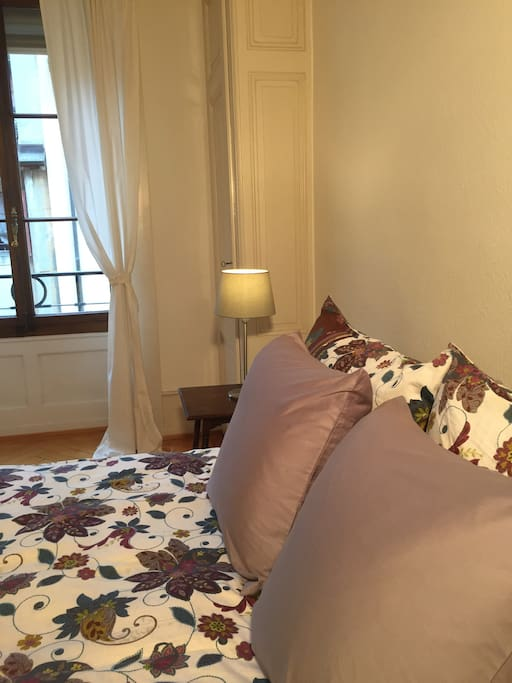 Large bedroom with Queen size bed and one set of linens provided; plenty of pillows. Bright with view of the interior garden.