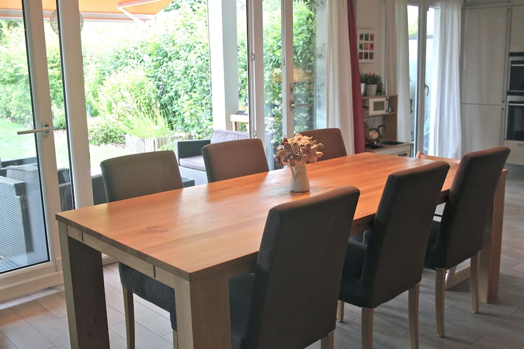 Family dining area opening onto large garden with seating and further dining