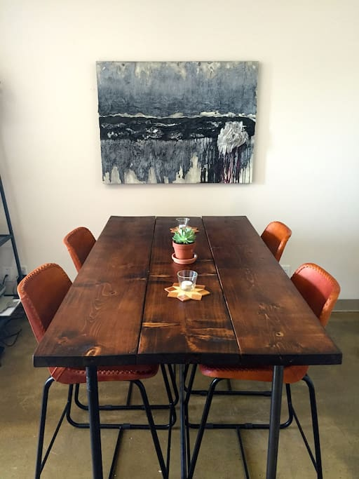 Handmade table with contoured leather high chairs.