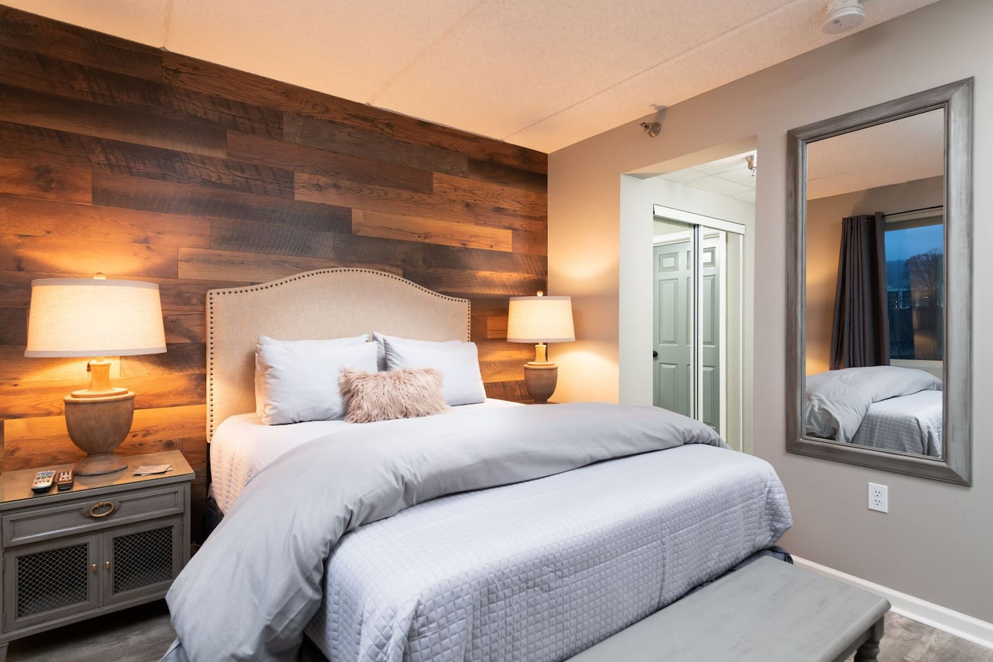 """Bedroom 1: Queen Bed with barn wood wall, 50"""" TV, and private attached bath with vanity and separate toilet and tub/shower combo."""
