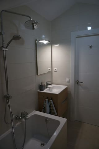 Bathroom with built-in toilet, shower / hot-tub and sink