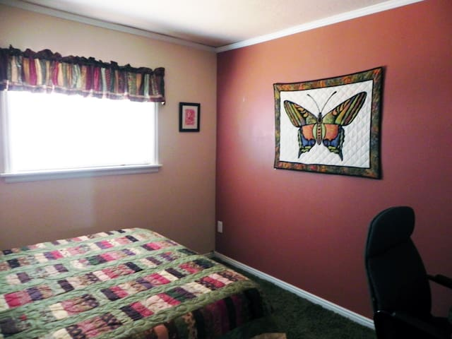 The rooms are decorated with quilts and curtains made by Kathy, including this butterfly wall hanging.