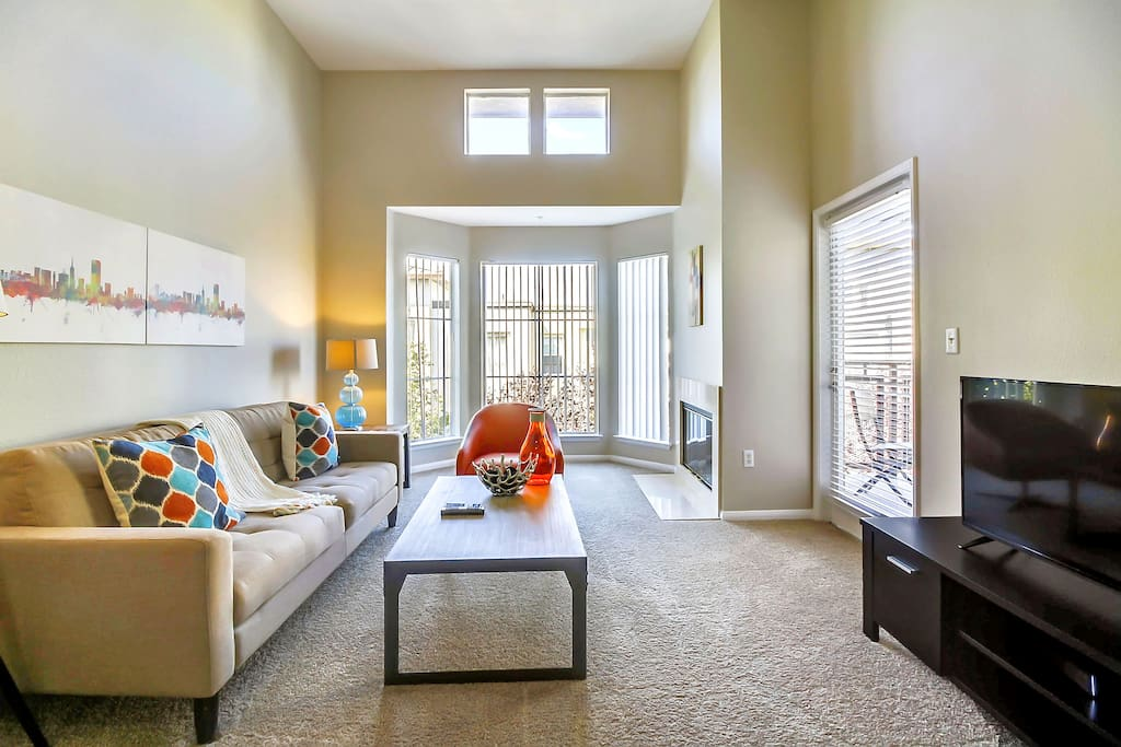 Living room with high ceilings, lots of natural light, media center and beautiful views from