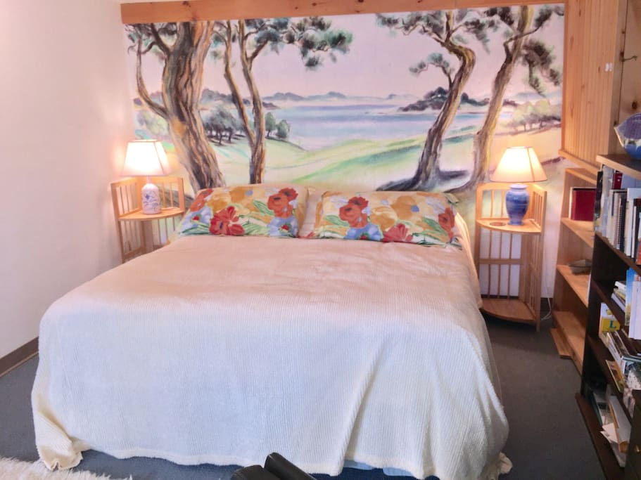 King size bed with a mural on the wall behind it