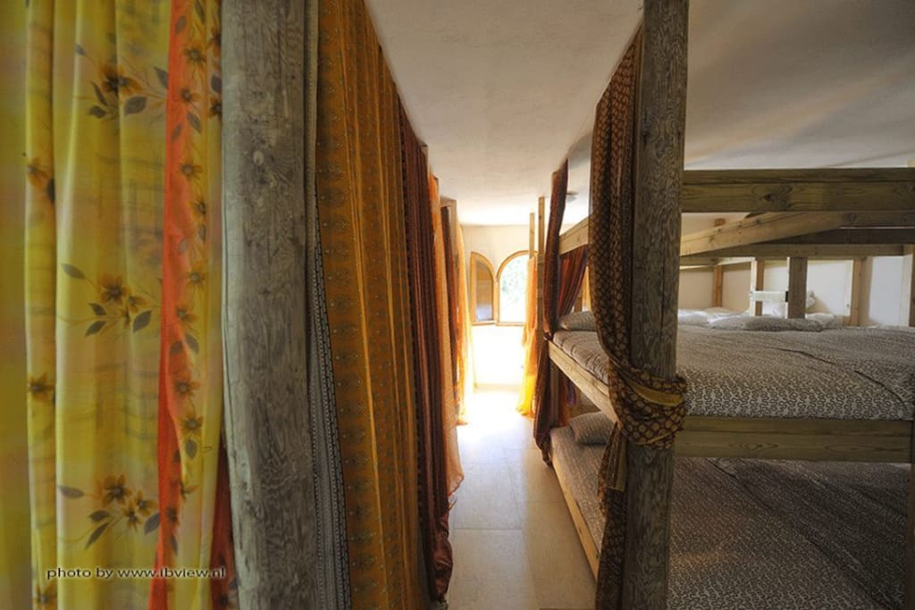 The bunk bed room with wooden beds and saris to provide privacy