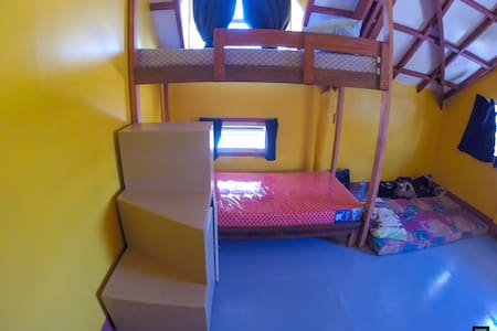 Cozy cheap bed in yellow dorm room on Malapascua